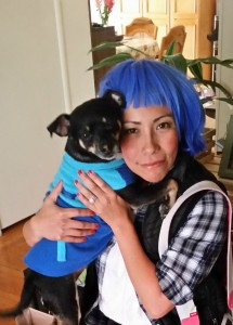 Girl with blue hair and her dog hugging her