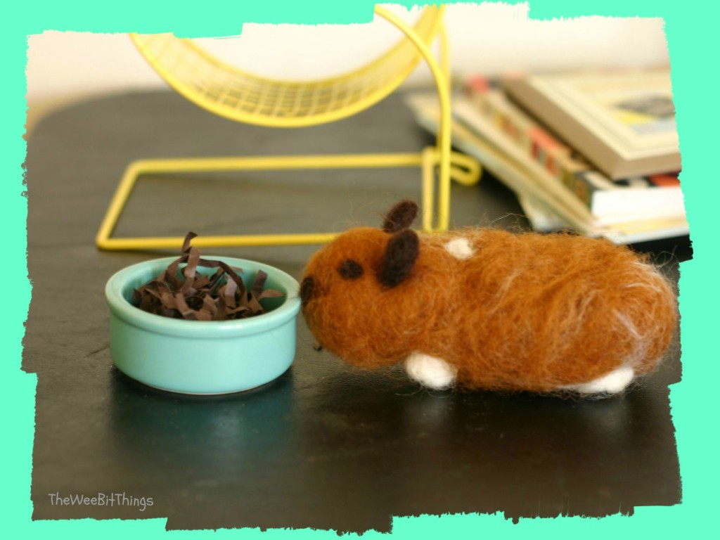 Image of a wool felt hamster approaching his food bowl